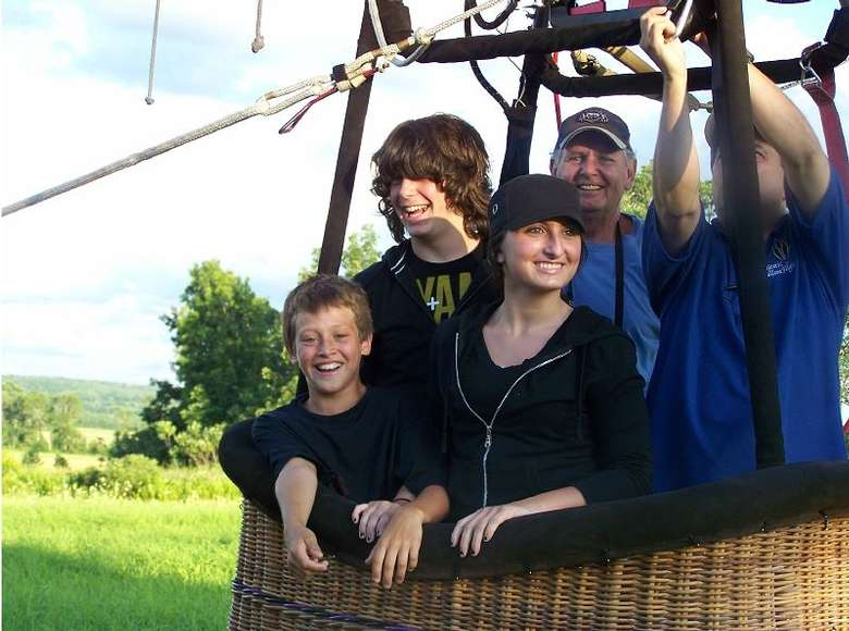group of people in a hot air balloon basket ready for a ride