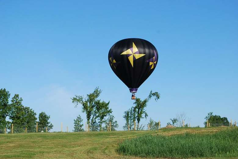 black hot air balloon with yellow pinwheels getting ready to land in a field