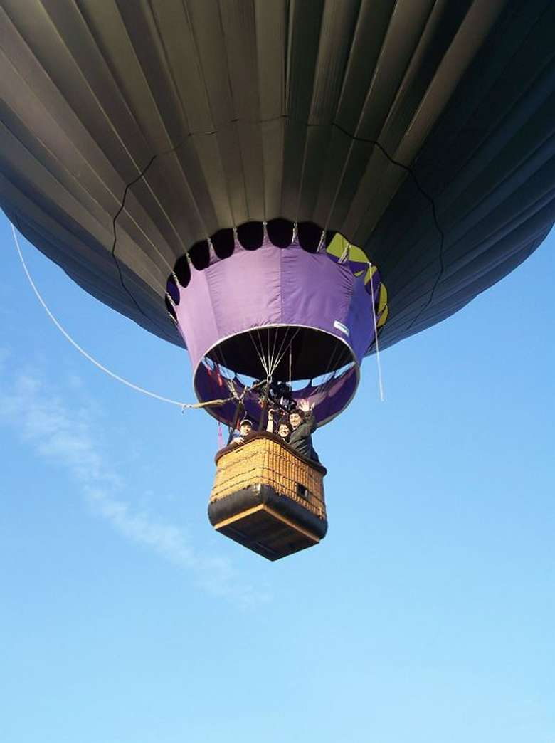 basket of a hot air balloon in flight with a blue sky in the background