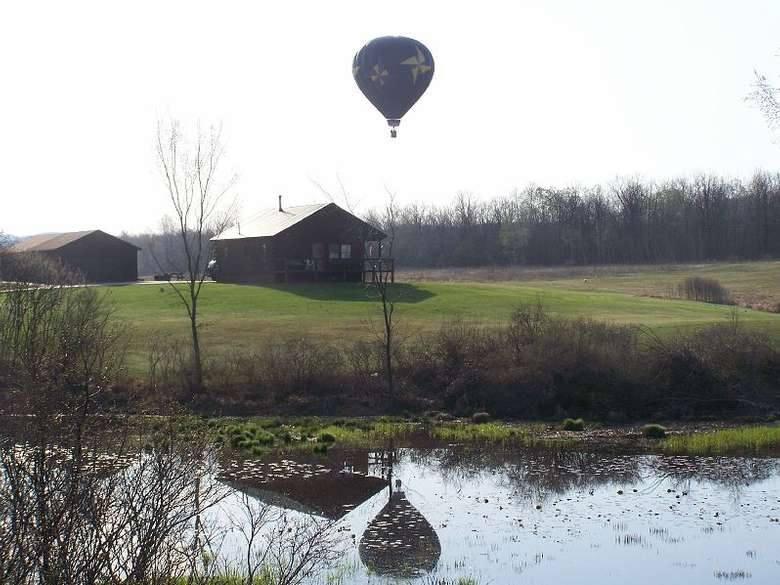 hot air balloon in flight reflected in a body of water