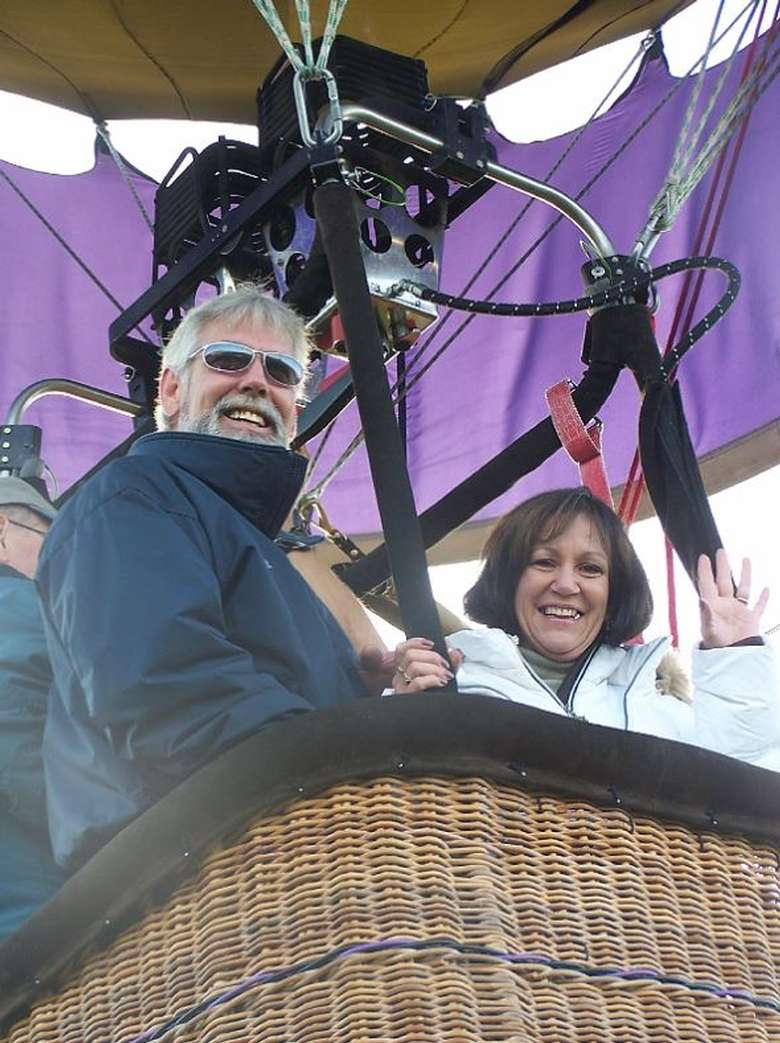 two people riding in a hot air balloon basket and smiling