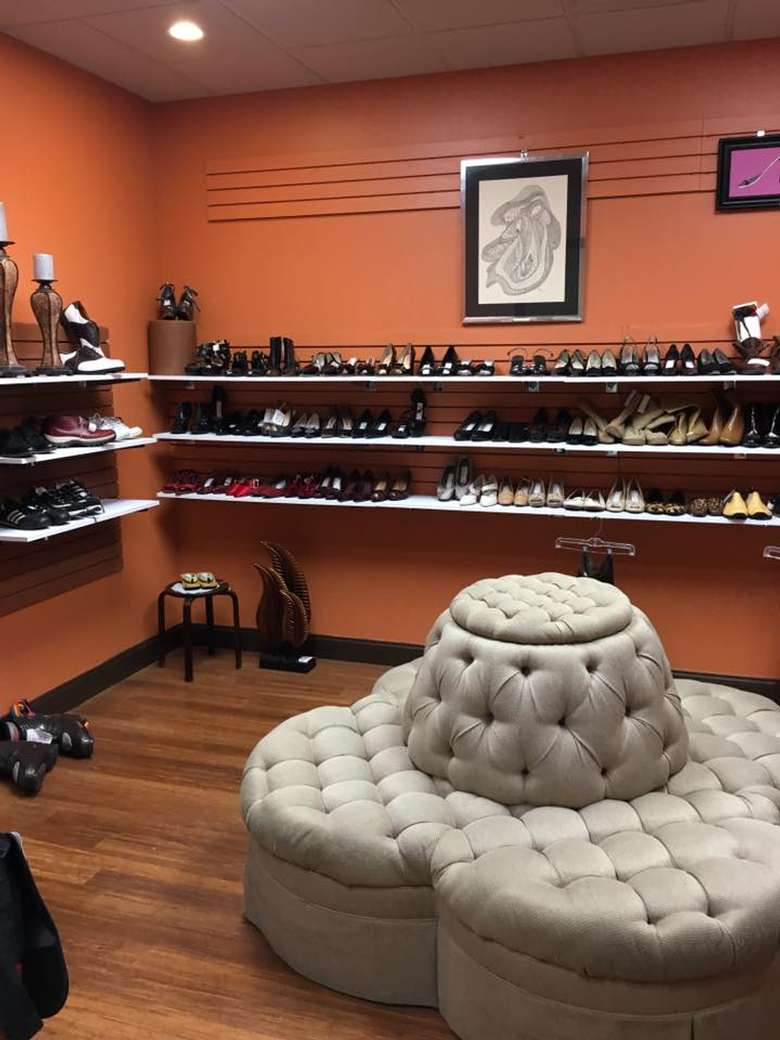 shoe section of a store with shelves full of shoes and a seating area