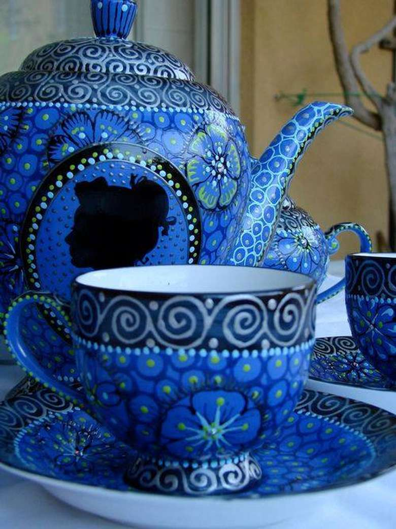 a blue teapot and matching cup and saucer