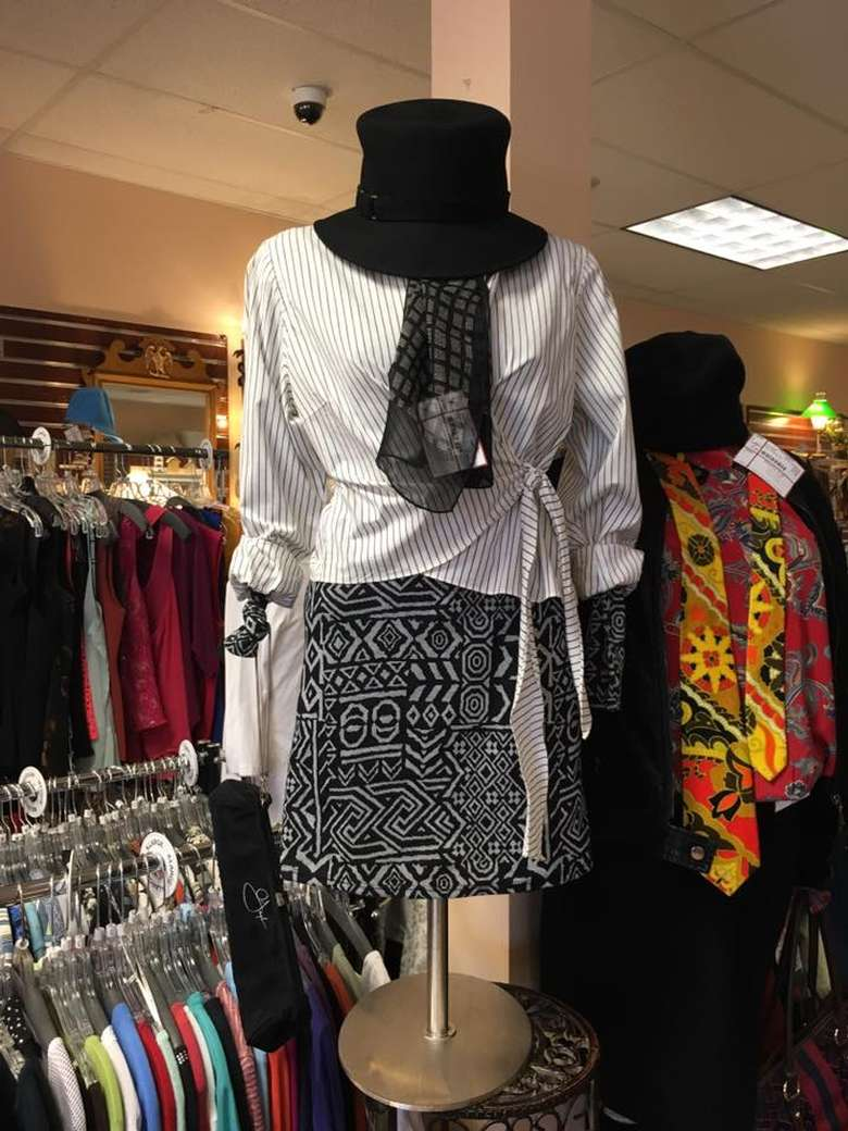 mannequin wearing a white top, black and white skirt, and a black hat and scarf