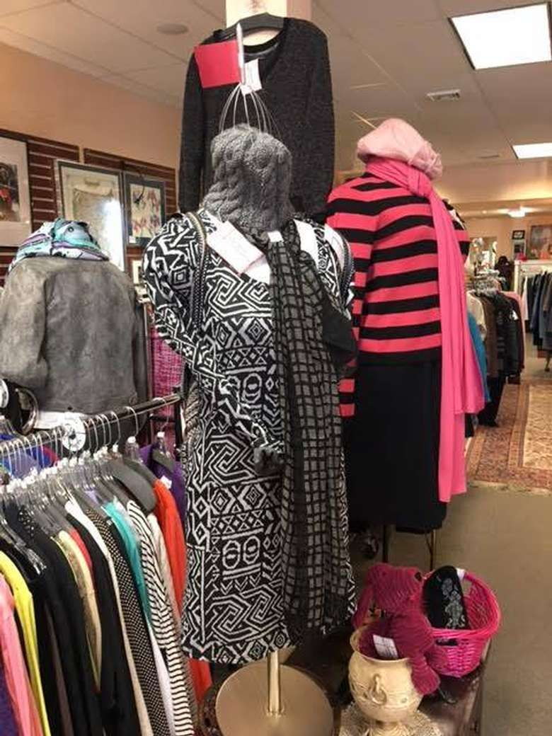 two mannequins, one wearing a black and white dress with a long scarf and the other wearing a pink and black striped shirt with a black skirt