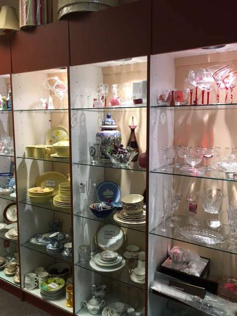 shelves full of antique glassware sorted by color