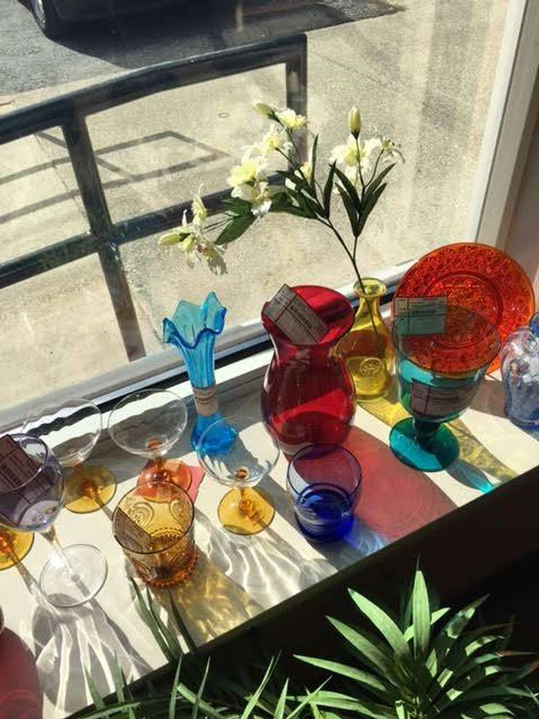 colored glassware on a windowsill including vases, stemmed, and stemless glasses