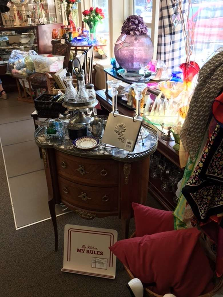 antique items in a consignment shop, including glassware and furniture