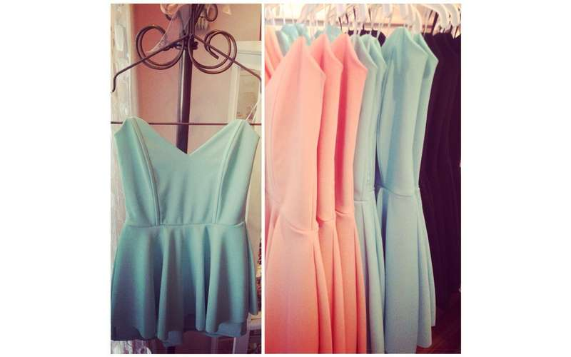 pink and light blue dresses on a clothes rack in a store