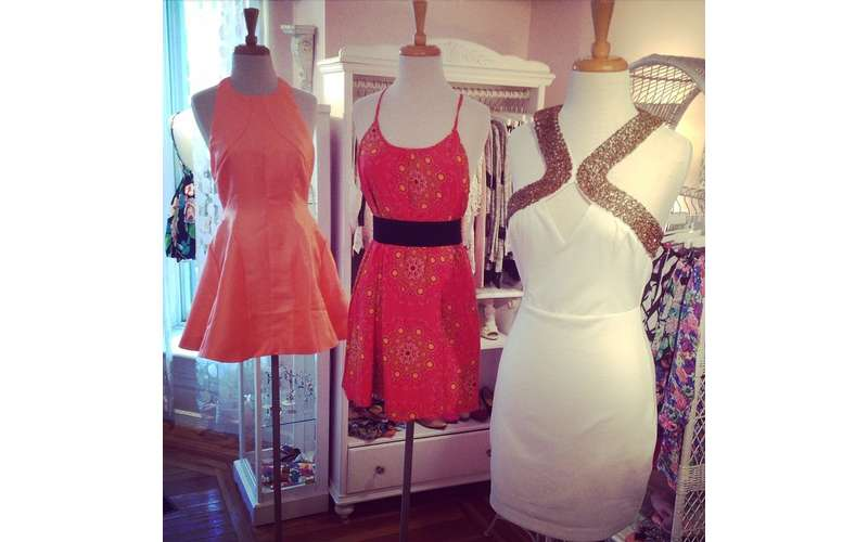 a shorter pink dress, a red dress, and white dress on display inside a store room
