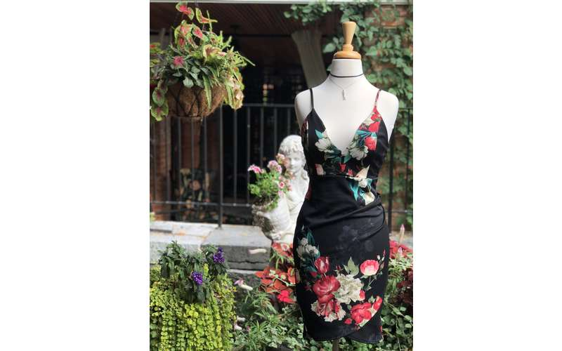 a floral and black dress on display outside