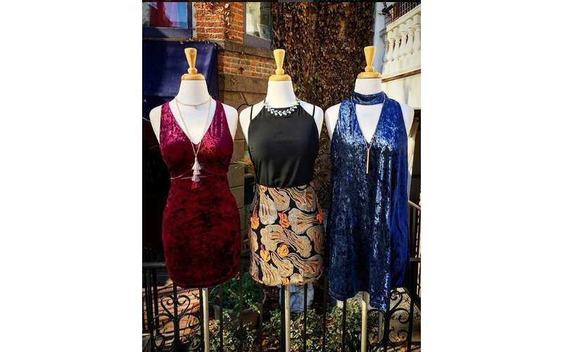 three colorful dresses on display in a row outside