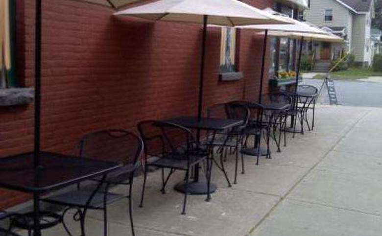row of patio tables with umbrellas along a sidewalk