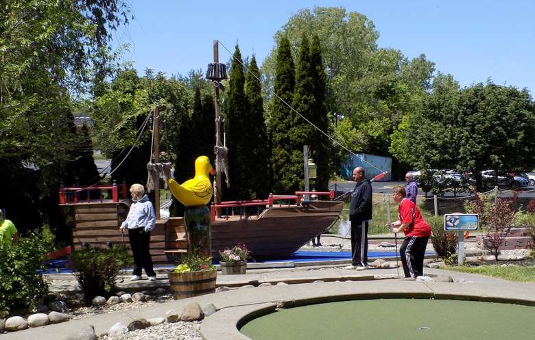 family golfing by pirate ship
