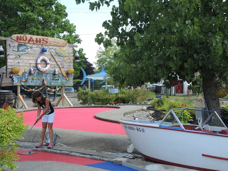 girl playing mini golf by fake boat