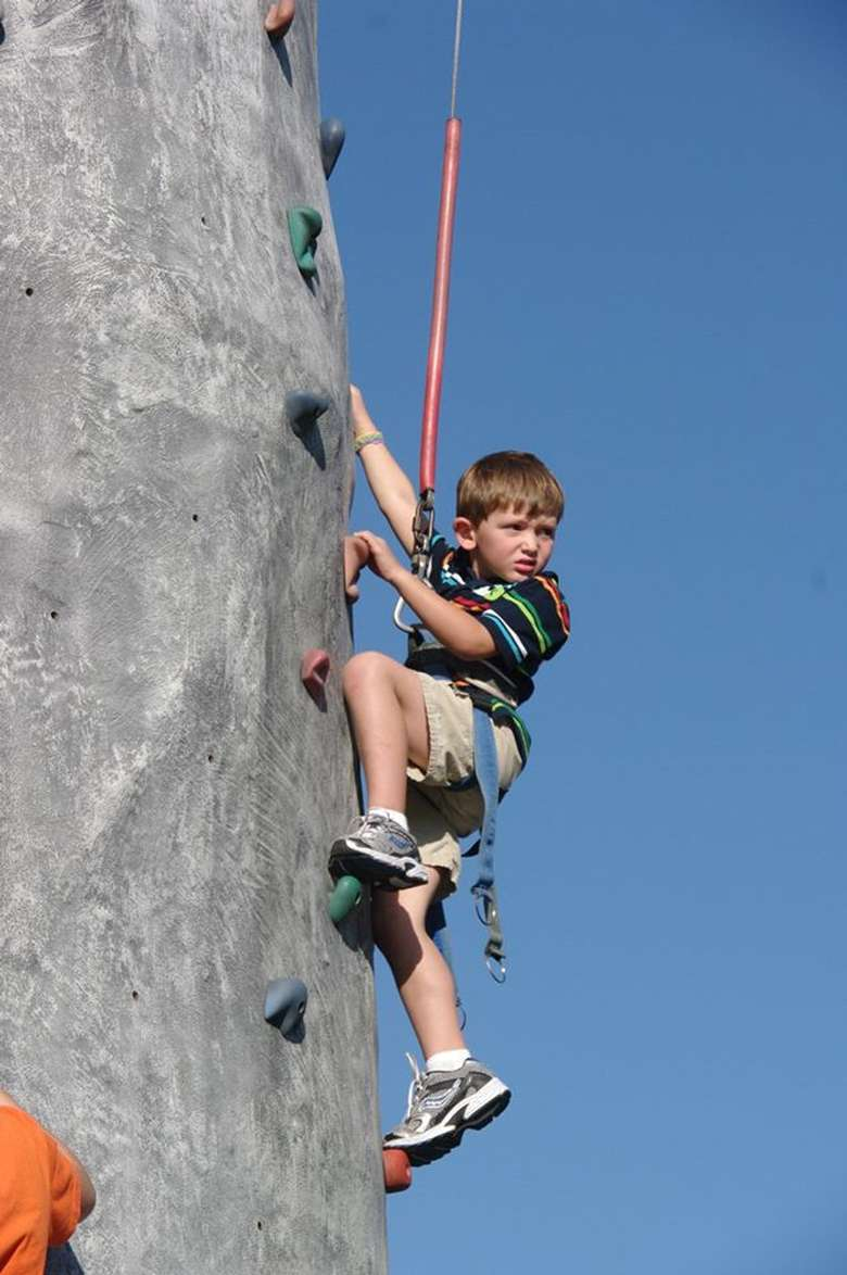 boy up in the air on a rock wall