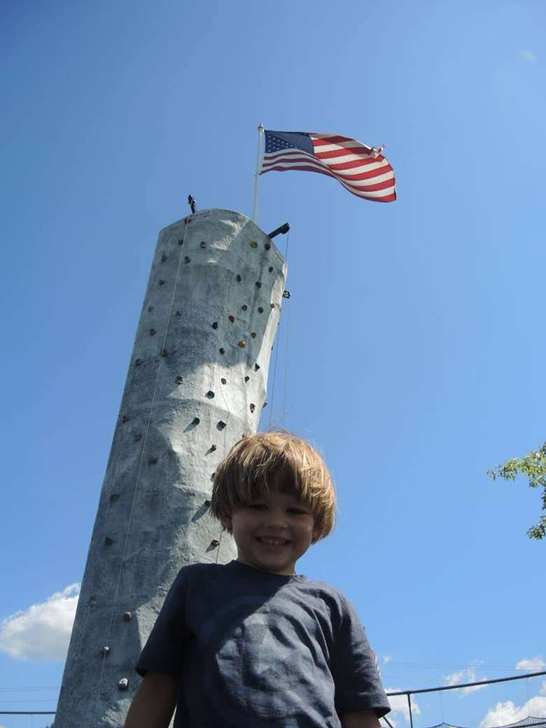 boy smiling in front of rock wall with a flag at the top