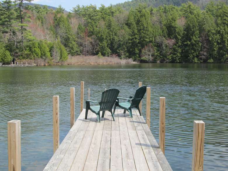 two adirondack chairs at the end of a dock