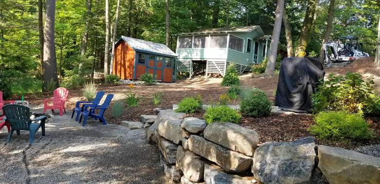 yard with adirondack chairs, a fire pit, a grill, and a shed