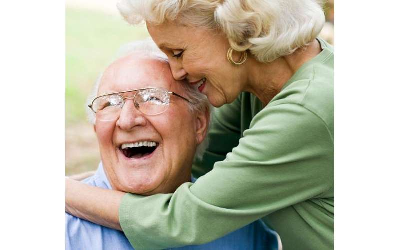 an elderly couple smiling and embracing