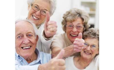 four elderly people smiling and giving thumbs up