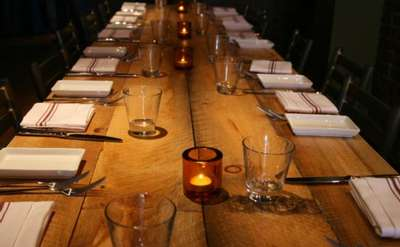large wooden table with napkins and empty glasses at each seat
