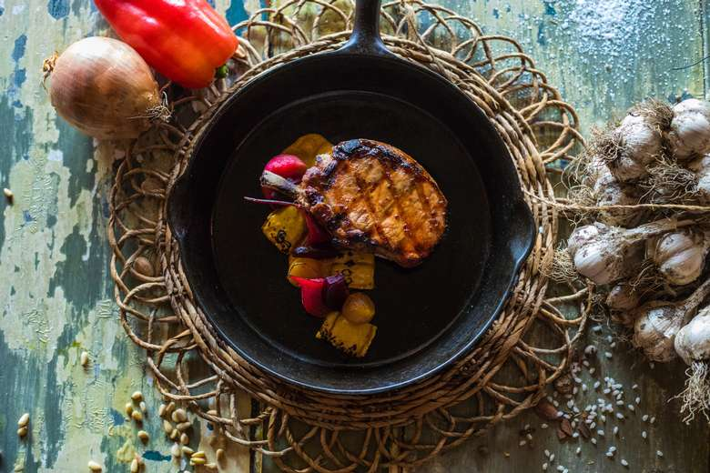 pork chop in a skillet with fruit