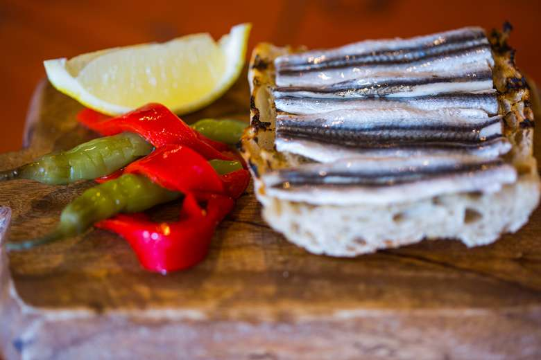 bread with anchovies, plus asparagus, a lemon wedge, and red peppers on the side