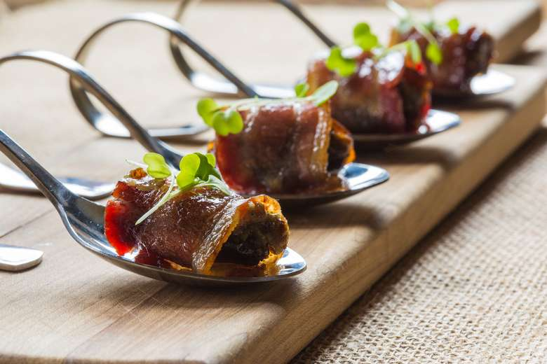 four bacon wrapped dates, each on a spoon