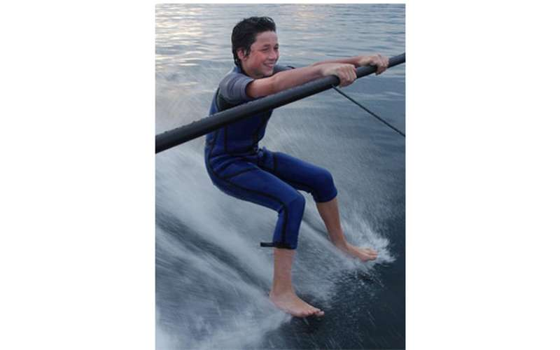 Boy barefoot skiing on a boom