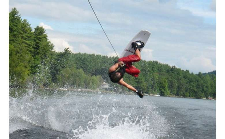 Young man jumping upside-down on a wakeboard