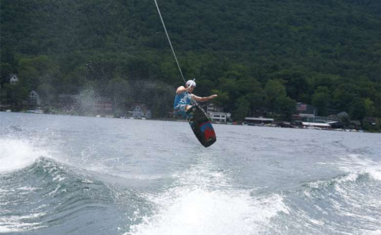 Young man doing a trick on a wakeboard.