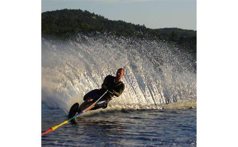 Man slalom waterskiing with water spraying behind him