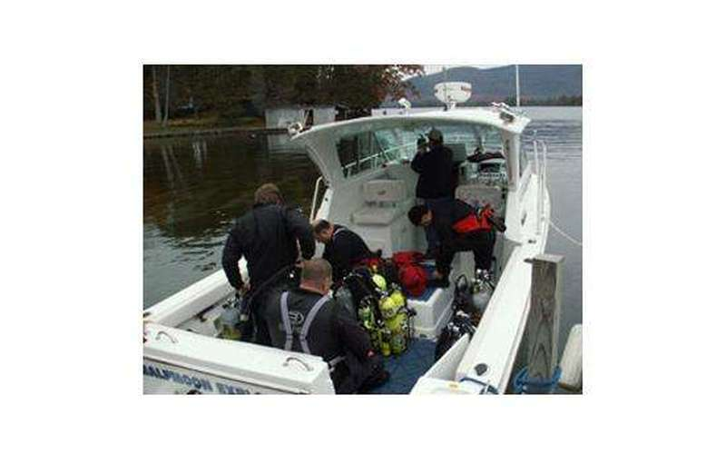 Four divers getting their scuba gear on in a boat in preparation for a dive