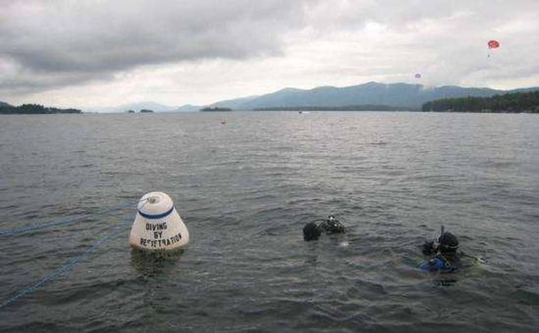 Two scuba divers at the surface of Lake George with a diving buoy