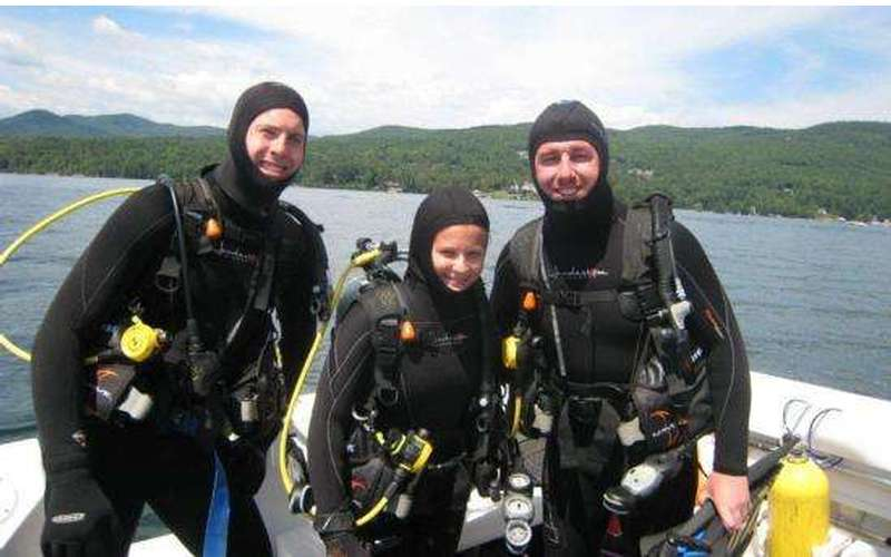 Three people in scuba gear getting ready for a dive in Lake George