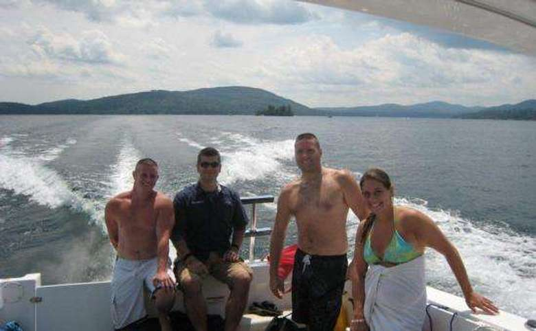 Four people in bathing suits in a boat on Lake George