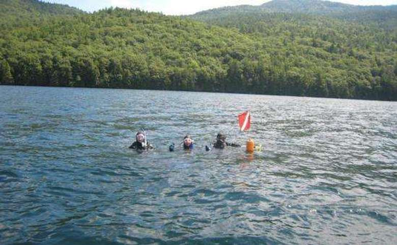 Three divers in Lake George with a dive flag and buoy