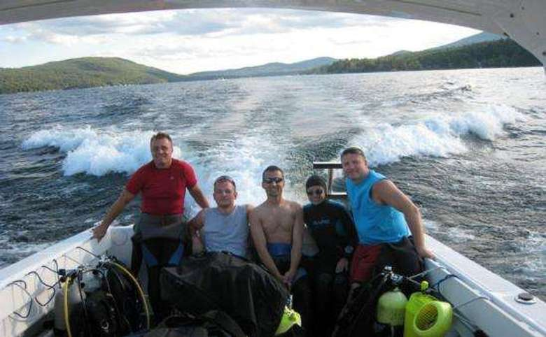 Five people in the back of a moving boat on Lake George