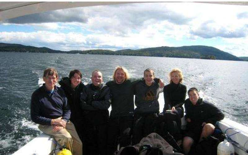 Seven people in the back of a moving boat on Lake George