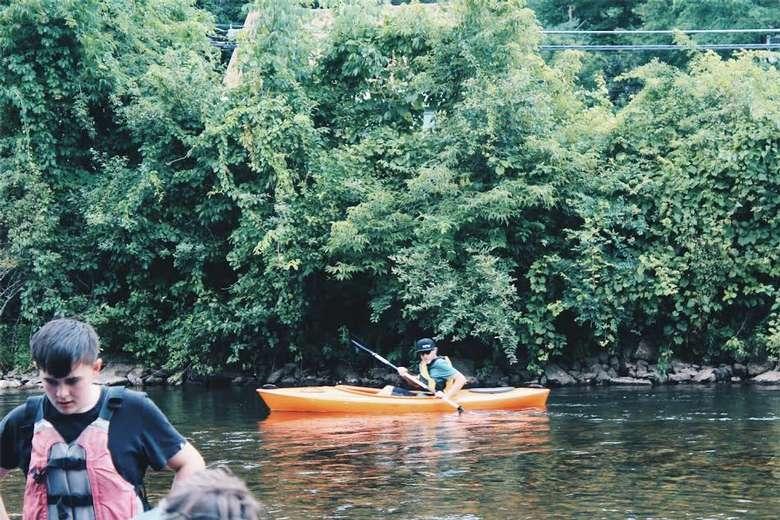 man kayaking in an orange boat