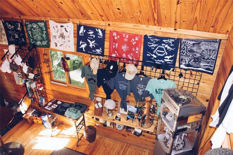 souvenir shop with t-shirts, hats, bandannas, and other items