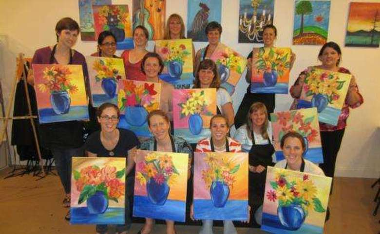 group of people posing with paintings after doing a paint and sip