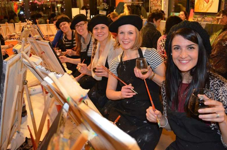 group of women in black aprons and hats painting during a paint and sip