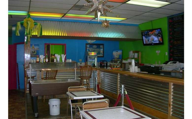 Interior view of dining area, looking from front to back, there are tables and chairs, a counter with chairs, bright blue and green walls, and a TV hanging on the green wall, to the right.