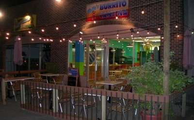 The entrance to Pablo's Burrito Cantina in the evening. There are patio lights over an outdoor patio with several tables and chairs.