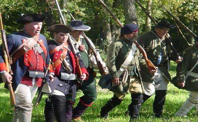 Costumed re-enactors carrying muskets