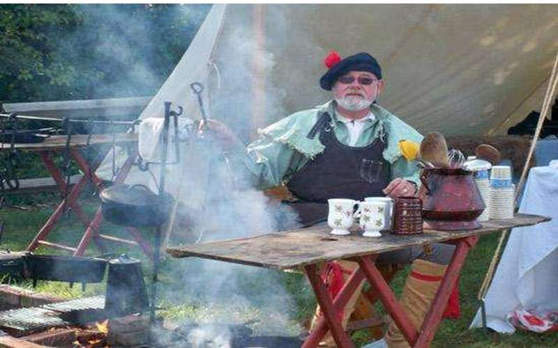 A costumed reenactor cooking over a fire