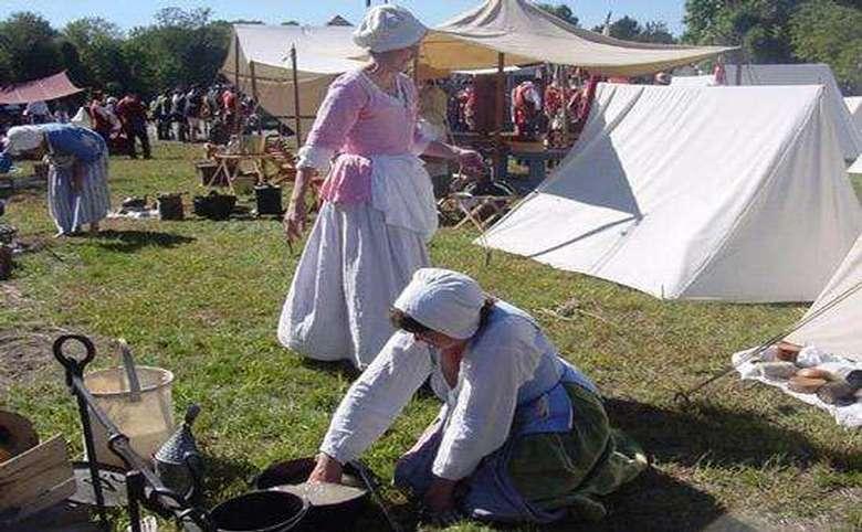 Two costumed reenactors doing chores