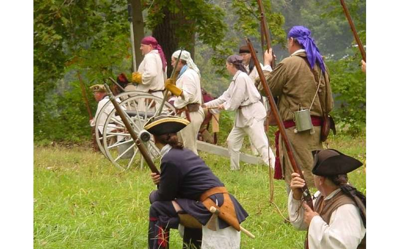 Costumed reenactors portraying a battle scene